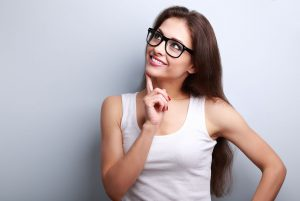 41664987 - healthy young thinking woman in glasses looking up on blue background with empty copy space